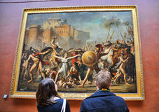 Tourists look at the paintings at the Louvre Museum Stock Images