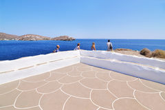 Tourists looking the Aegean sea at Panaghia Chrisopigi church Sifnos Greece royalty free stock photography