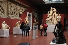 Tourists looking at antique sculptures. Royalty Free Stock Image