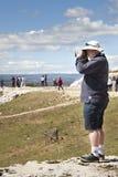 Tourists looking with binoculars Roman amphitheater. Syracuse, Sicily. Italy. Stock Photo