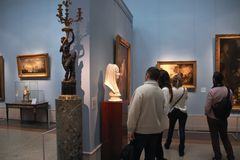 Tourists looking at the bust of a woman and paintings Royalty Free Stock Photo