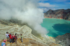 Tourists looking down to Ijen Crater or Kawah Ijen. Royalty Free Stock Images