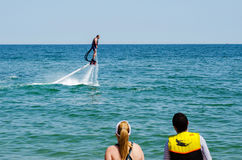 Tourists looking at a flyboard demonstration Stock Images