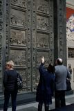 Tourists looking at the gate with a bas-relief of the Renaissance. Royalty Free Stock Image