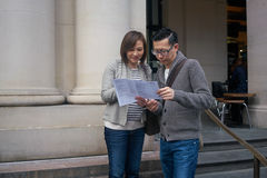 Tourists looking at map. Man and women tourists looking at map royalty free stock photos
