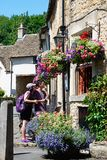 Tourists looking at pub menu, Castle Combe. Royalty Free Stock Image