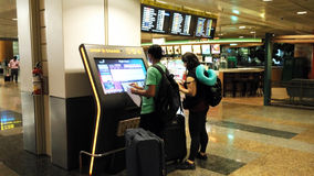 Tourists looking at screens in airport. Tourists looking at information flight on screens at airport. Singapore airport is one of the main aviation hubs in Stock Image