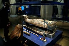 Tourists looking at the stand with the ancient Egyptian sarcophagus. Stock Images