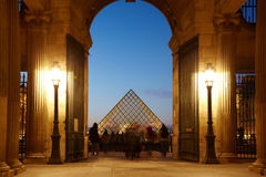Tourists in Louvre look round Louvre pyramid Royalty Free Stock Images