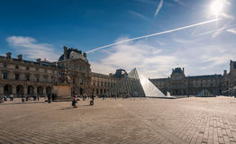 Tourists in the Louvre's central courtyards with the Louvre pyramid and palace. Stock Image