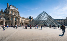 Tourists in the Louvre's central courtyards with the Louvre pyramid and palace. Stock Photo