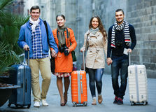 Tourists with luggage walking by street Stock Photos