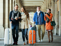 Tourists with luggage walking by street Royalty Free Stock Image