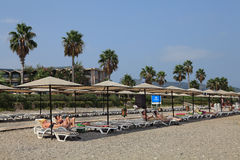 Tourists lying on the loungers private beach in Mediterranean resort. Royalty Free Stock Image
