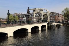 Tourists on the Magere Brug bridge in Amsterdam. Amsterdam, The Netherlands - March 31, 2017: Tourists stand on the Magere Brug bridge across the Amstel canal in stock photo