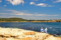 Tourists on Maine coastline. A view of two tourists sitting on the rocks of the beautiful coastline of Maine at Schoodic Point, on a clear, summer day Royalty Free Stock Photo