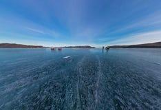 Tourists make the transition ice on Lake Baikal ice at sunset. W Stock Image