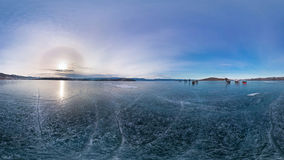 Tourists make the transition ice on Lake Baikal ice at sunset. W Royalty Free Stock Photography