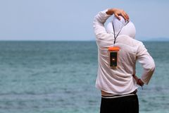 Tourists man wear a raincoat and hanging smartphones in the waterproof bag standing on the beach. In Thailand royalty free stock image