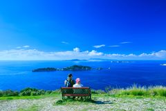 Tourists, a man and a woman sitting on a bench, admiring the won royalty free stock image