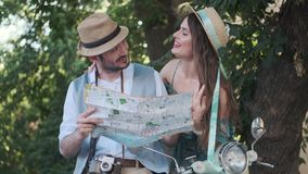 Tourists with a map of the city in their hands. young couple travelers on a trip. Couple of tourists are exploring the map in travel. a young woman and a man stock video footage