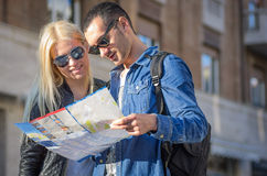 Tourists with map. Couple of tourists with map in the center Royalty Free Stock Image
