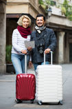 Tourists with map and luggage Royalty Free Stock Photos
