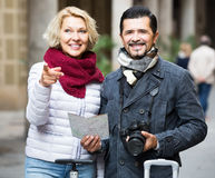 Tourists with map and luggage on city street Royalty Free Stock Image