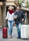 Tourists with map and luggage on city street Stock Photos