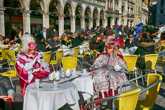 Tourists and masked persons in colorful costume sitting in cafe Royalty Free Stock Photo