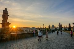 Tourists meet the morning dawn on the Charles Bridge in Prague Stock Photo