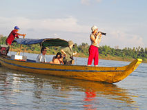 Tourists on Mekong river. Tourists on a boat in Cambodia while spotting rare Irrawaddy river dolphins. Near the city of Kratie Royalty Free Stock Images