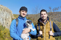 Tourists men in the autumn  mountain with their dog Royalty Free Stock Image