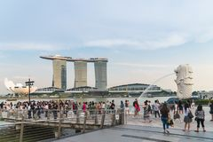 Tourists on merlion park in Singapore. Many tourist on Singapore merlion park with merlon statue and marina Bay Sands building behind Royalty Free Stock Photos