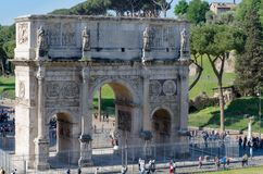 Tourists mill around the Arch of Constantine as seen from a view. Point in the Colosseum early one Spring morning Stock Photo
