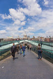 Tourists and Millennium Bridge. LONDON, UK - JULY 9, 2014: Tourists walking on the Southbank side of the Millennium Bridge, with St Pauls cathedral in background Royalty Free Stock Photos