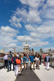 Tourists and Millennium Bridge. LONDON, UK - JULY 9, 2014: Tourists walking on the Southbank side of the Millennium Bridge, with St Pauls cathedral in background Royalty Free Stock Photo