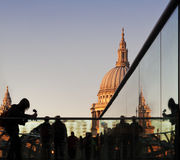 Tourists on Millennium Bridge, St Paul's, London. Tourists at dusk on Millennium Bridge, with a detail of St Paul's Cathedral in the background Stock Image
