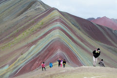 Tourists on Montana De Siete Colores near Cuzco. Seven colour mountain in Peru. Tourists climbing to the top Royalty Free Stock Photography