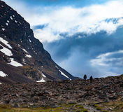 Tourists in a mountain pasage. A couple of tourists is walking over a stone field in a mountain passage in Swedish arctic mountains. Dramatic clouds and light Royalty Free Stock Images