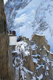 Tourists at the mountain top station of the Aiguille du Midi 3842 m in French Alps watching climbers exercise Stock Photos