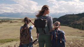 Tourists in the mountains. a young mother and her daughters teenagers in a hike. woman with children admiring the. Stunning views of the mountains stock video footage