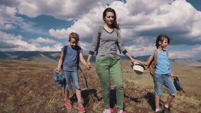 Family of tourists on a journey. mother with two daughters in the campaign. children with backpacks admire the view of. Tourists in the mountains. a young mother stock video footage