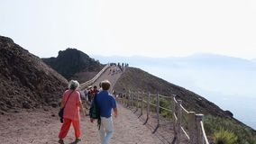 Tourists moving along walkway around Vesuvius volcano, passing its sharp cliffs. Stock footage stock video footage