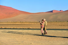 Tourists in the Namib-Naukluft National Park, Namibia, Africa. Couple of tourist, men and women taking a pictures on the smartphones in Sossusvlei at sunrise royalty free stock photography