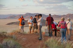 Tourists in the namibian landscape. SOSSUSVLEI PARK, NAMIBIA -  MAY 6, 2014: a group of tourists during a safari stop in the namibian landscape. They are Stock Photos