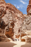 Tourists in narrow passage of rocks of Petra canyon in Jordan Royalty Free Stock Photography