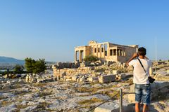 Ancient Greek Temple of the Erechtheum. Tourists near Ancient Greek Temple of the Erechtheum on Acropolis at sunset Royalty Free Stock Photo