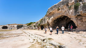 Tourists near artificial caves in Syracuse city Royalty Free Stock Photo