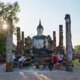 Tourists near Buddha statue in old Buddhist temple ruins Stock Images